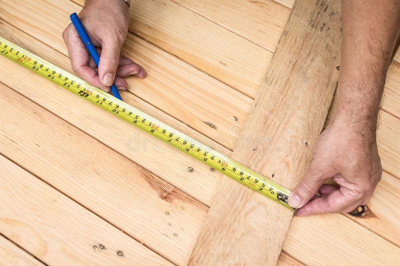 мужские-руки-измеряя-деревянный-насти